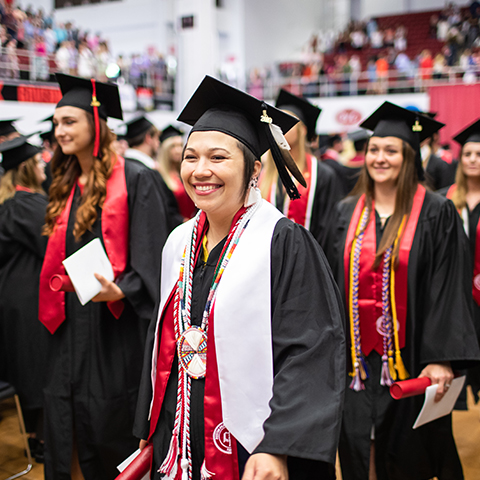 student smiling at APSU commencement ceremony