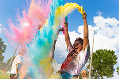 Student throws color packet into the air at Gov Color Run