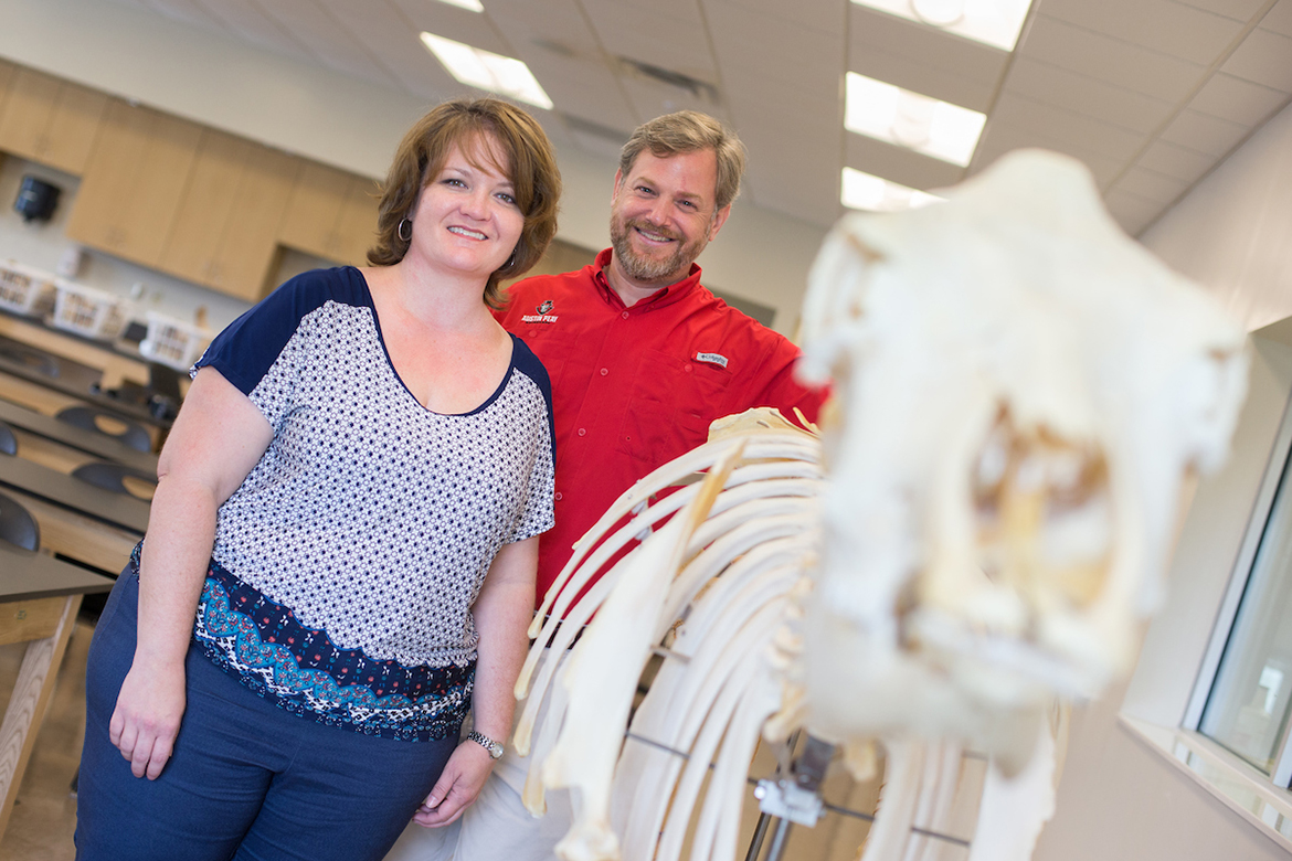 two professors with a cow skeleton