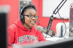 Student sits in communication radio lab