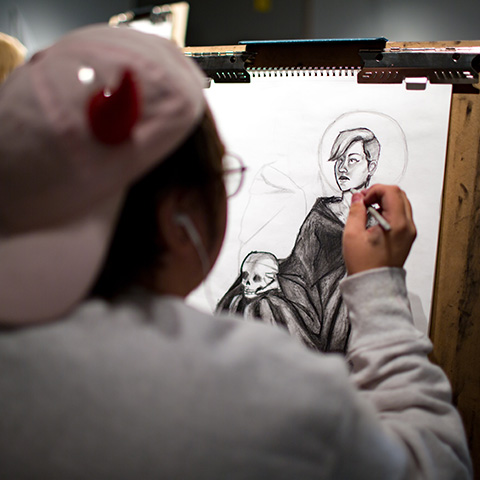 Art student works on portrait in Art and Design building