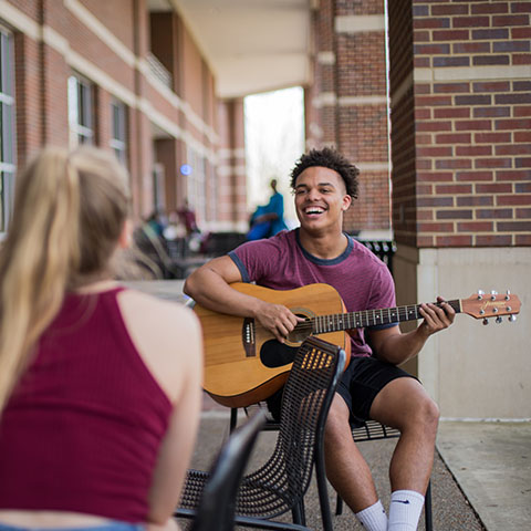 Students outside UC with guitar