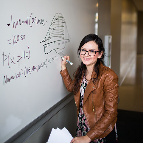 Math student writes on white board in Maynard math and science building