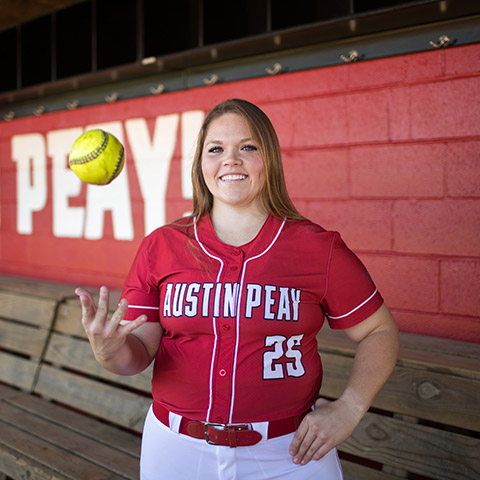 Alexis Hill poses for a photo in softball dugout