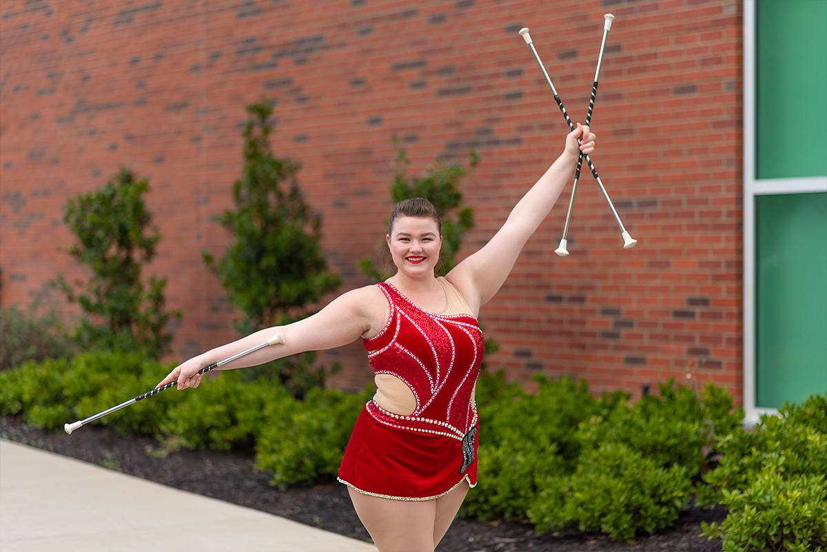 Izzy Melvin poses in front of Art and Design building with twirling batons
