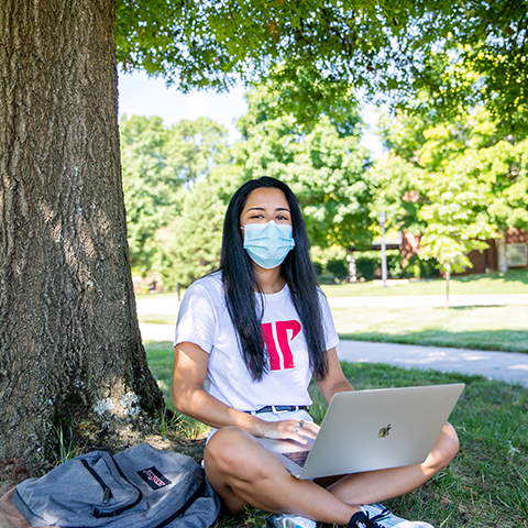 Student studies under shade tree with mask on