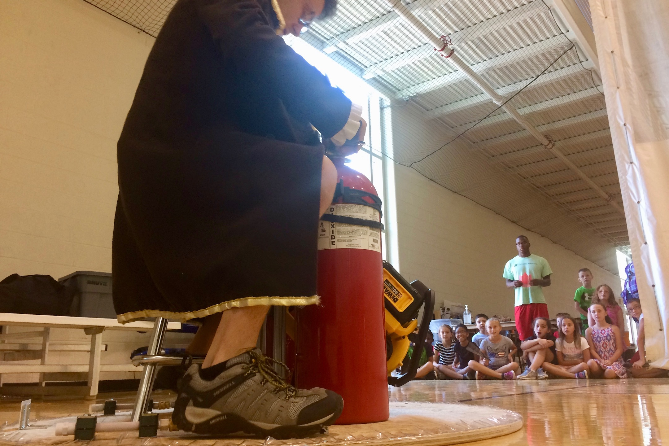 APSU's Bryan Gaither prepares to don an Iron Man mask and his across the gym floor on his homemade hovercraft. Attendees of the university's Junior Govs Summer Camp are in the background.
