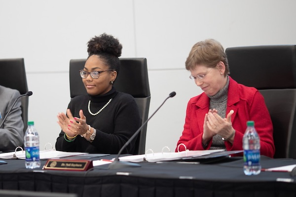 Celeste Malone sits at table with Board of Trustees