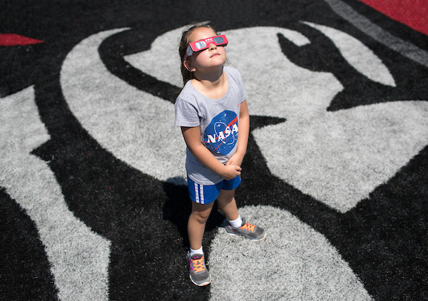 Girl looks at Eclipse through safety glasses