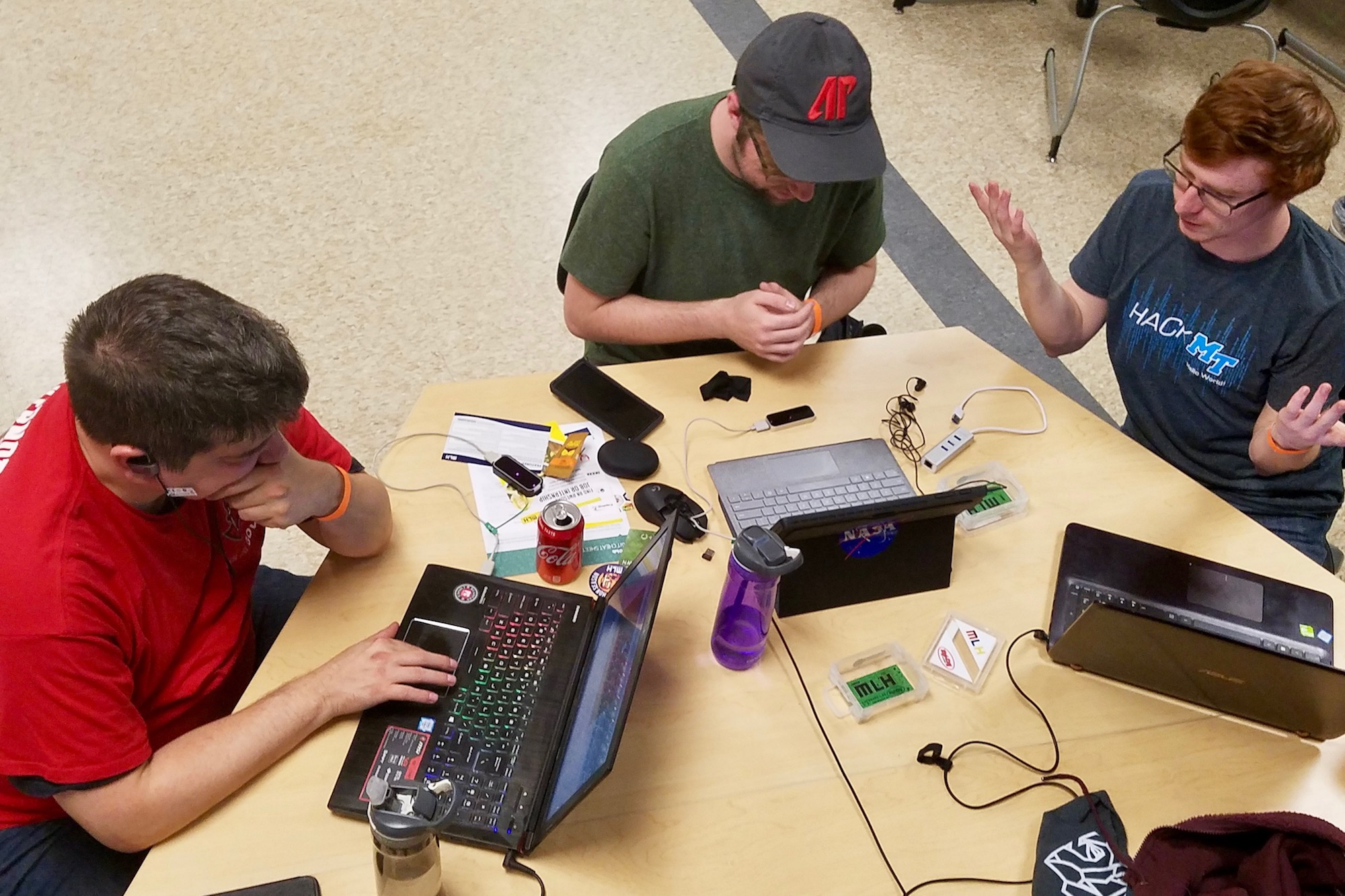 "From the left, Nathan Nickelson, Dylan Engle and Aidan Murphy work on their hack, ""LeapLearning: Sign Language."""