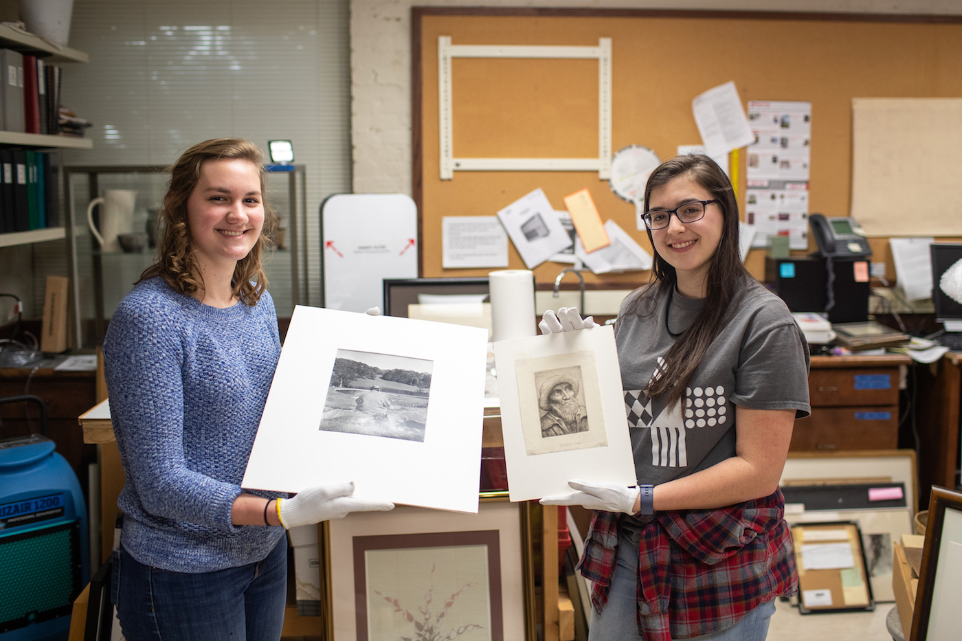 Art students Sarah Potter and Katherine Tolleson hold their discoveries. Potter is holding a Philippe Halsman photo print of Winston Churchill, and Tolleson is holding a drypoint by Alphonse Legros.