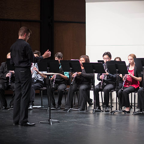 Music student conducts ensemble during performance