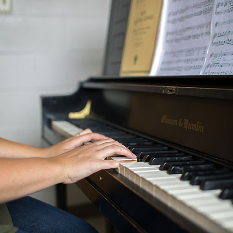 Susannah White plays piano in practice room