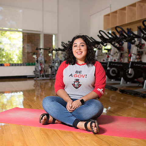 Jenny Hernandez sits on yoga mat in workout room.