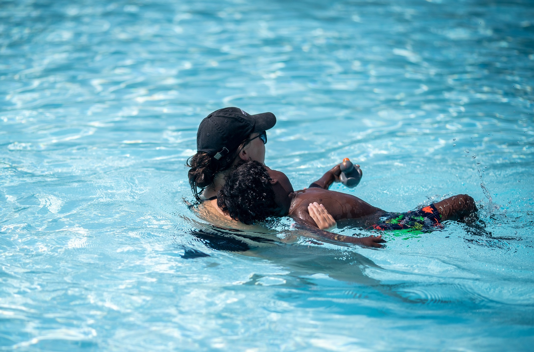 swim instructor teaching child to float on back
