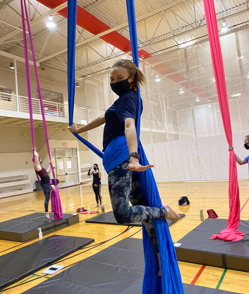student in Aerial Silks class on blue silk in a seated pose